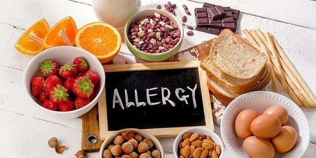 Food allergy. Allergic food on  wooden background. View from above